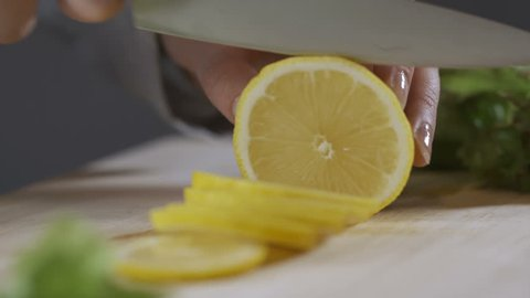 Woman cutting a lemon on the chopping board. Hand sliced lemon on chopping board closeup. Juicy lemon cut into slices. The sharp chef knife slices the citrus fruit. Cutting some lemons for a tea.