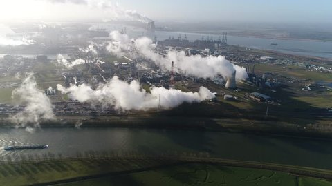 Aerial footage of nuclear power plant and cargo vessel barge moving over canal a thermal power station in which the heat source is a nuclear reactor this plant is located in a heavy industrial zone 4k
