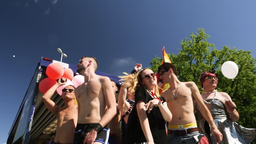 STRASBOURG, FRANCE - JUN 10, 2017: excited dancing of gay men and women people with rainbow flag behind in slow motion at Lesbian Gay Bisexual Transgender LGBT visibility march pride on gay truck