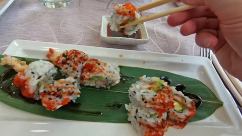 SLOW MOTION: hand feeding on uramaki of shrimp tempura, cheese, avocado and tobiko caviar dipping in soy sauce bowl. Japanese fusion food, Asian cultures. Healthy food, light diet concept.