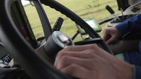 Hands of middle aged caucasian driver on big round steering wheel of tractor riding on farm grass field, close up