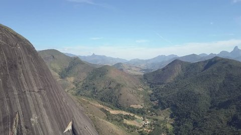 Aerial view of mountains in Petropolis, near Rio de Janeiro, Brazil. Green trees of tropical forest in a valley. Beautiful sunny day with blue sky