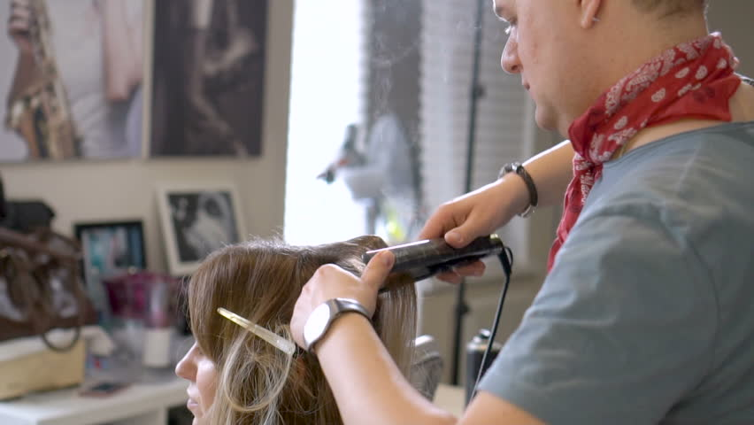 Guy does the hairstyle to the girl in the hair salon. Man who works as a stylist. Adjusting the hairstyle at prom. Preparing the appearance for the celebration. Girls in beauty salon. Women's leisure.