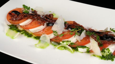 Italian Caprese salad, with sliced mozzarella cheese, tomatoes, decorated with parmesan cheese, dried tomatoes, black olives and thyme, served in Italian restaurant, loop, ProRes source codec