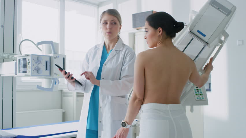 In the Hospital, Female Patient Listens to Mammography Technologist / Doctor Uses Tablet Computer, Explains Importance of Breast Cancer Prevention. Mammography Procedure. Shot on RED EPIC-W 8K Camera
