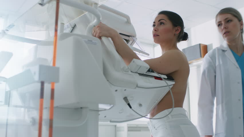 In the Hospital, Mammography Technologist / Doctor Pushes Button on Mammogram Machine Activating Female Patient Scan. Friendly Doctor Explains Importance of Breast Cancer Prevention Screening. 4K UHD.