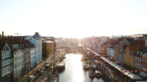 BAcklight sunset footage from Copenhagen, Denmark. bridge in Nyhavn New Harbour canal and entertainment district. Aerial Video footage view from the top. forward movement. Sunset golden time light