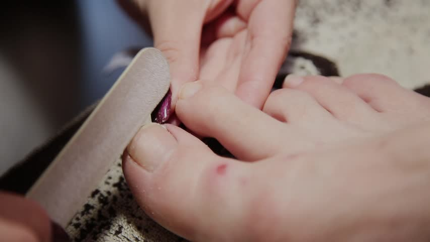 Caring about the girl legs pedicure, polish, beautiful lights. Pedicures in the salon. The master cares for the nails and feet of the client, doing the pedicure. Peeling feet pedicure procedure