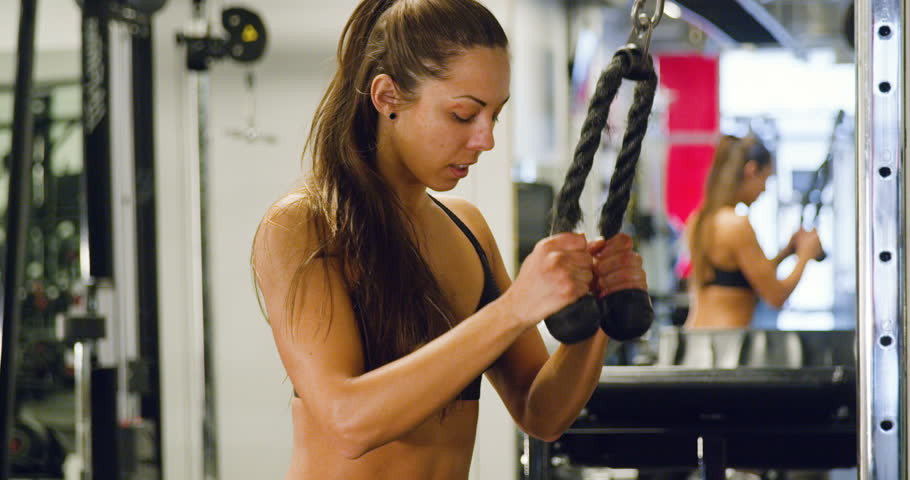 Focused woman training triceps muscles pulling cable machine in gym | Shutterstock HD Video #1012095416