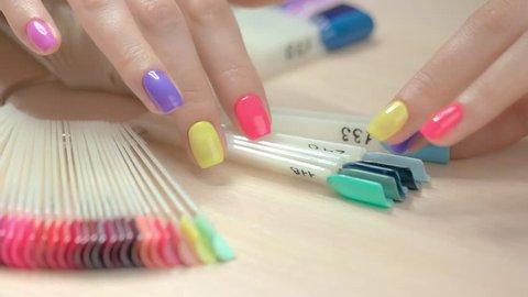 Nail polish samples in female hands. Nail polish testers and young woman manicured hands. Girl choosing perfect nail varnish color.