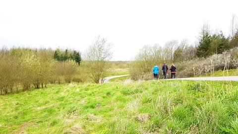 A group of people walking along a gravel path  through the countryside on an overcast windy day.