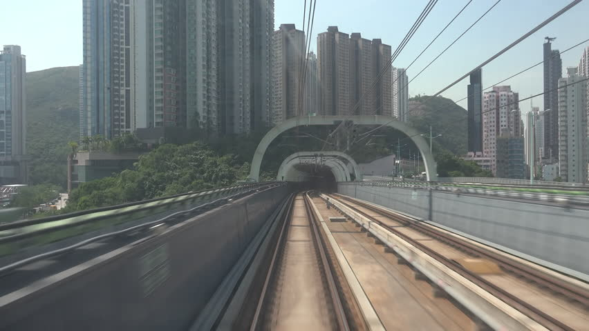 Train moves along metro or subway railroad half-open tunnel and passes by Hong Kong city buildings and skyscrapers. Electric rapid public transport, urban mass transit railway system or MTR. | Shutterstock HD Video #1012131206