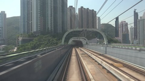 Train moves along metro or subway railroad half-open tunnel and passes by Hong Kong city buildings and skyscrapers. Electric rapid public transport, urban mass transit railway system or MTR.