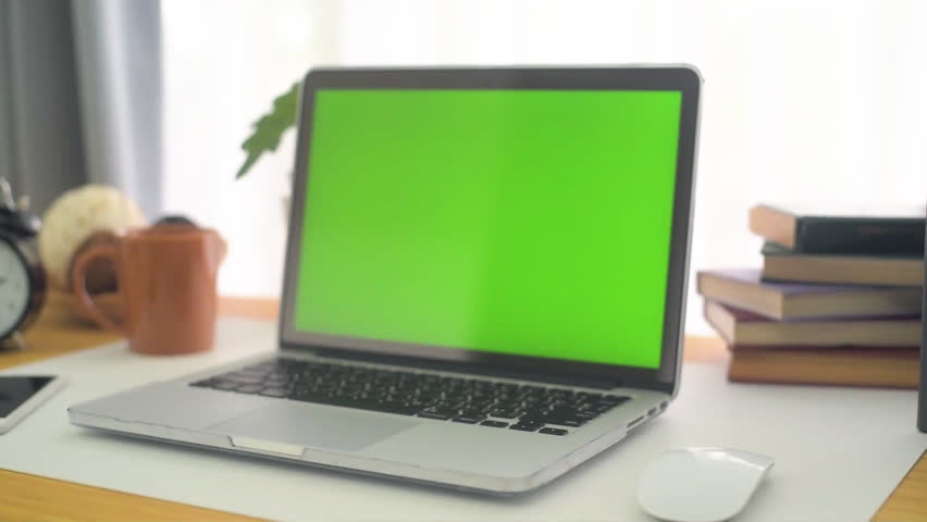 A laptop computer with a key green screen set on work office table. #1012148606
