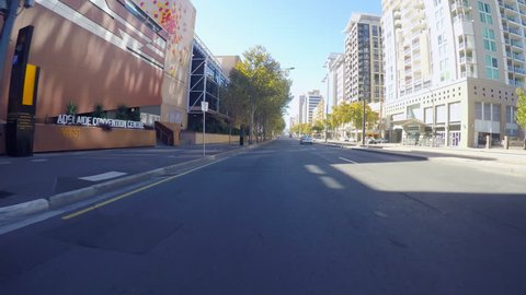 Adelaide, South Australia - April 29, 2018: Action camera vehicle POV driving along North Terrace past the Adelaide Convention Centre.