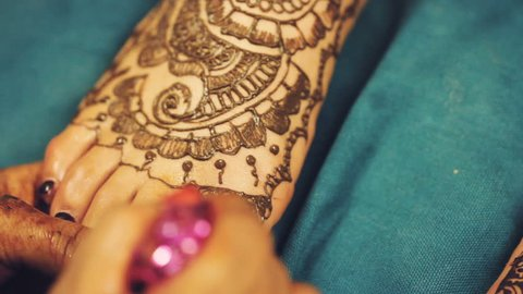 Henna artist (Mehndi) painting the tattoo pattern on the foot of indian bride on the indian wedding day