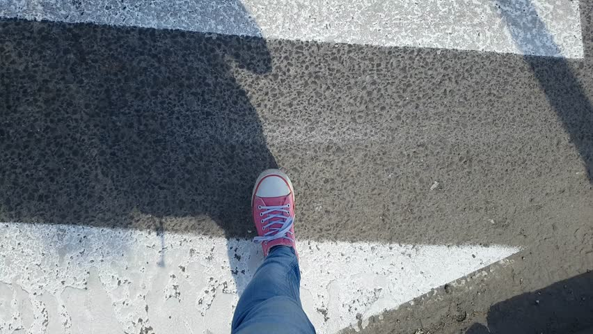 Female feet walking on the zebra crossing in pink sneakers and jeans. First person POV. | Shutterstock HD Video #1012161236