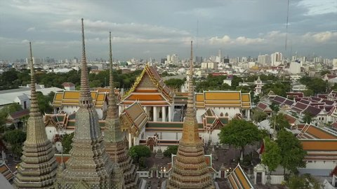 Wat Phra Kaew temple in Bangkok beautiful drone view in 4K. Aerial shot of amazing Thai Buddhist temple. Unique perspective close over golden roof and skyline background. Wat Pho