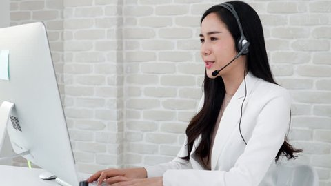 Beautiful Asian woman operator wearing microphone headset working in call center office talking with customer