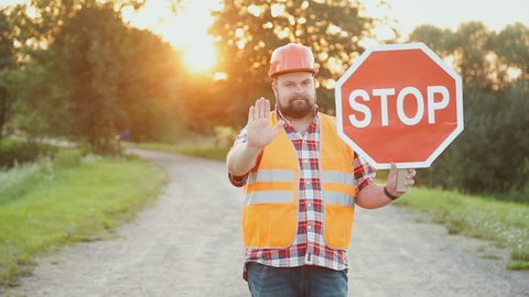 A construction road worker stopping traffic, holding a stop sign.