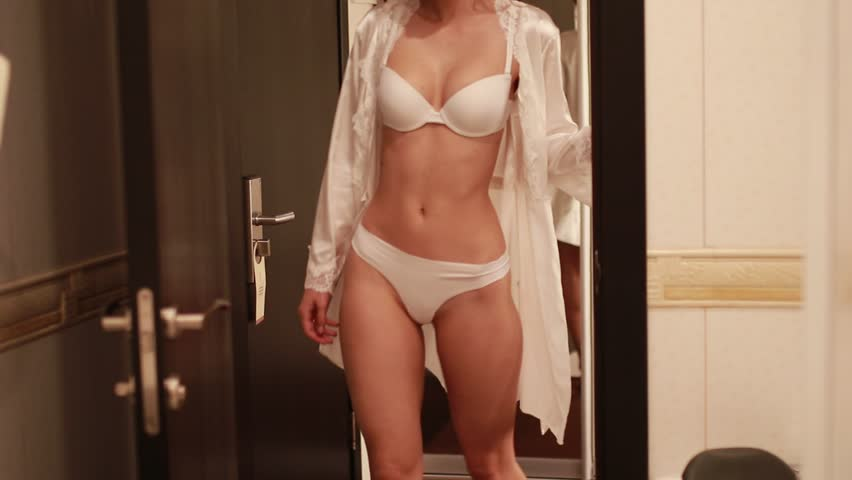 Happy bride in a white lingerie and peignoir goes to the bathroom in her wedding day.