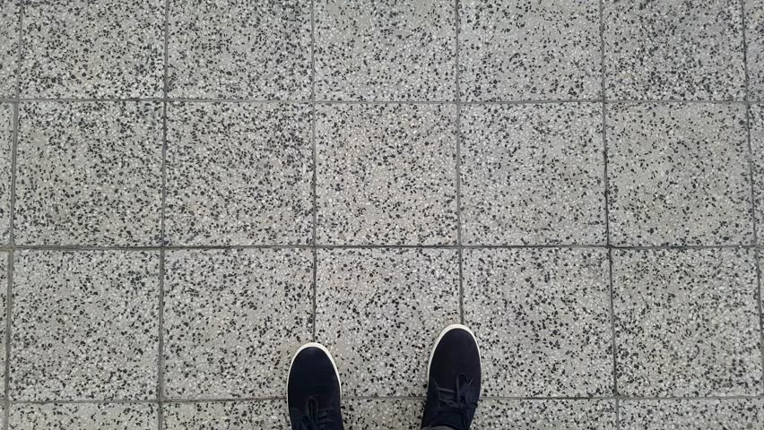 Male feet walking on the pavement in black shoes and pants. First person POV. | Shutterstock HD Video #1012191296