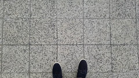 Male feet walking on the pavement in black shoes and pants. First person POV.