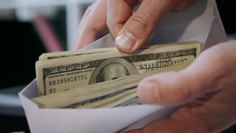 Close up of cash money in envelope in hands. Money bonus in paper envelope. Man holding envelope with dollar bills. World bribery. Scam and corruption concept. Credit company financial services