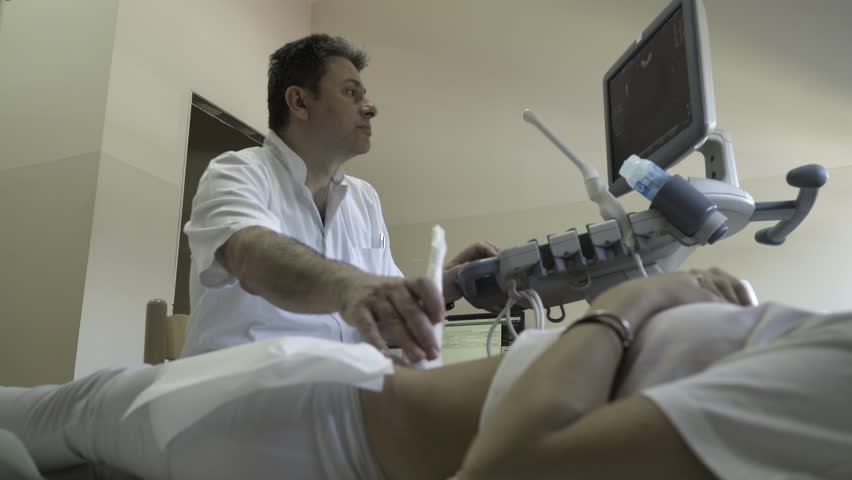 Male gynecologist using ultrasound and looking in monitor during gynecological examination of woman, doctor performs medical review while female patient lying in ambulance room at gynecology ward.
