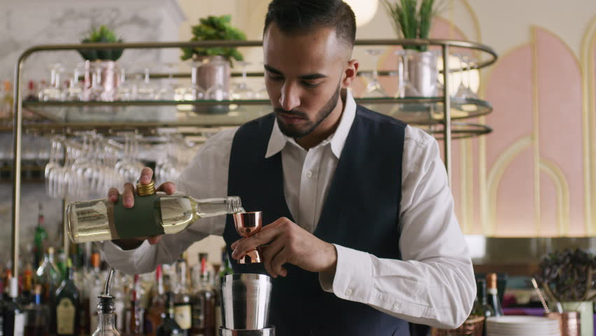 Bartender pouring liquor into shaker for cocktail. Restaurant cinematic scene. Shot with a RED camera.