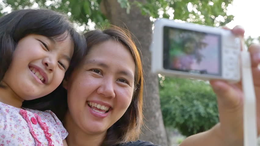 Asian mother and daughter taking selfie photograph together