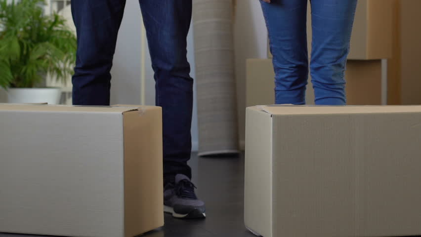 Young couple moving out apartment, carrying carton boxes, eviction through debts