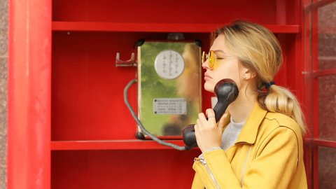 Portrait of handsome upset blonde woman finish talk on public payphone in red telephone box and going away worried unhappy face stylish female in cool sunglasses heard bad news sunny day light