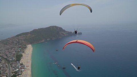 Tourists fly by paragliding over Cleopatra's beach