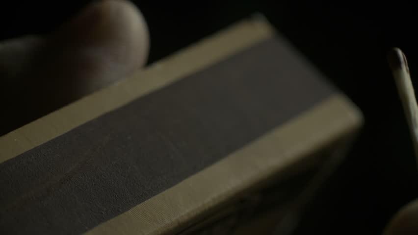 A macro shot of a matchbox with broken matchstick.
