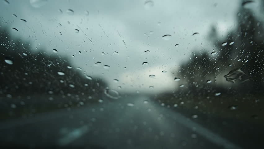 Driving in the rain view from inside car with rain drops on car windshield. Rain drops on window car windshield | Shutterstock HD Video #1012277996