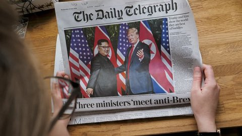 PARIS, FRANCE - JUNE 13, 2018: Woman reading The Daily Telegraph newspaper in the office showing on cover U.S. President Donald Trump meeting North Korean leader Kim Jong-un in Singapore