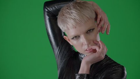 Portrait of blonde androgynous girl on a green-screen. She is holding hands near head and biting finger, looking at camera