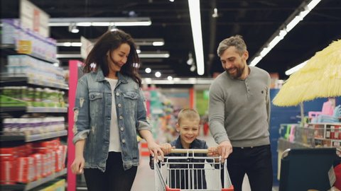Slow motion of happy family father, mother and child running through supermarket with shopping cart, smiling and laughing. Having fun in shop and people concept.
