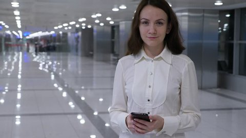 Young adult woman half-length portrait at dim airport passage, she look straight to camera with faint smile. Empty sterile area hall seen blurred on background. Brunette lady wear white shirt