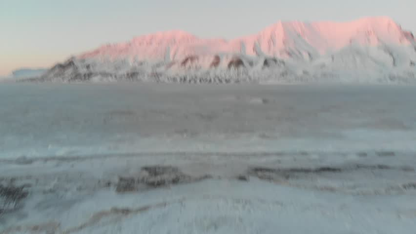 Longyearbyen, Svalbard aerial footage flying on top of the north pole arctic sea towards snow mountains during sunset | Shutterstock HD Video #1012304246