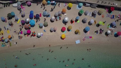 Tourist under parasol on crowded Greek beach, beautiful turquoise and blue water, swimmers, sunbathing. Picture perfect  top down. Colorful sunshades. beautiful bay. aerial drone shot from above