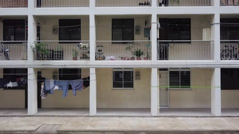Rising aerial shot up the facade of old low income housing apartments in  singapore