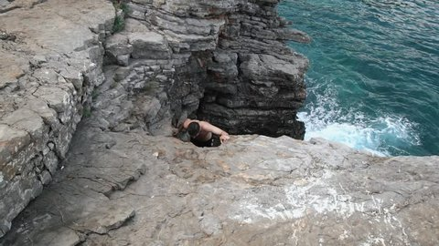 SLOW MOTION: Man climbing cliff at seaside. Young athletic shirtless male climbs rocky beach cliff.