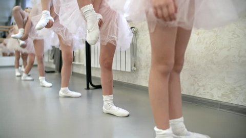 Legs of unrecognizable little girls using ballet barre to stretch legs for splits, dolly shot, camera moving backwards