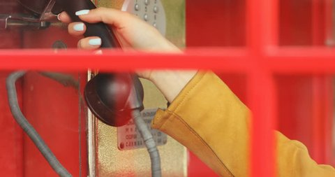closeup view of female hand taking black hanged telephone handset in red retro payphone call box and then looking at cameraa big big surprised eyes traveling attracrive blonde woman having fun
