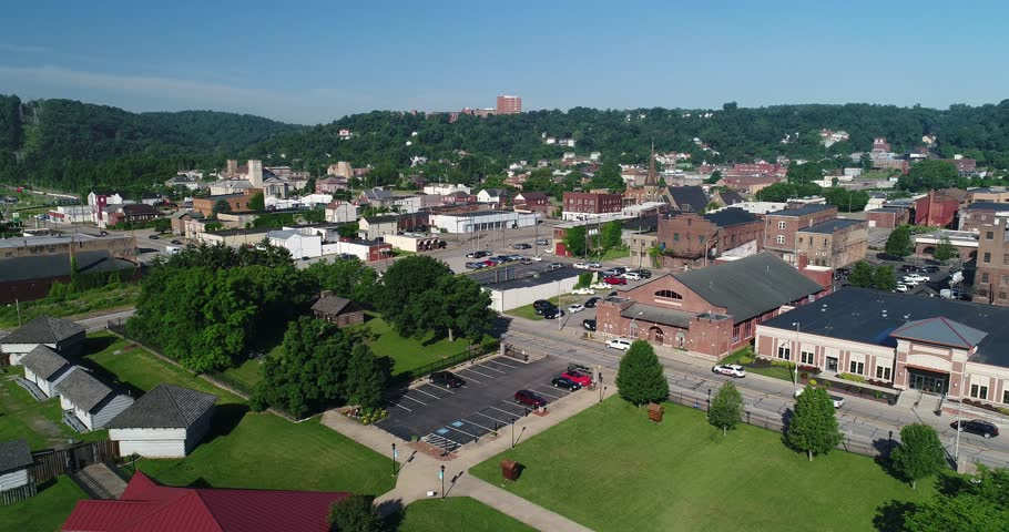 A slow forward aerial establishing shot (DX) of the small rust belt Ohio town of Steubenville on the Ohio River.
