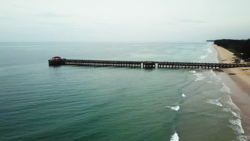 The tropical beach with a pier, fishing boats, shooting from air | Shutterstock HD Video #1012381016