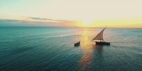 fishermen's wooden dhow sailing at sunset in Zanzibar