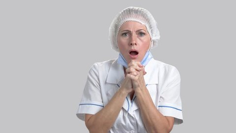 Scared horrified woman doctor on grey background. Female doctor looking shocked and stunned with hands on head. Doctor in full disbelief.